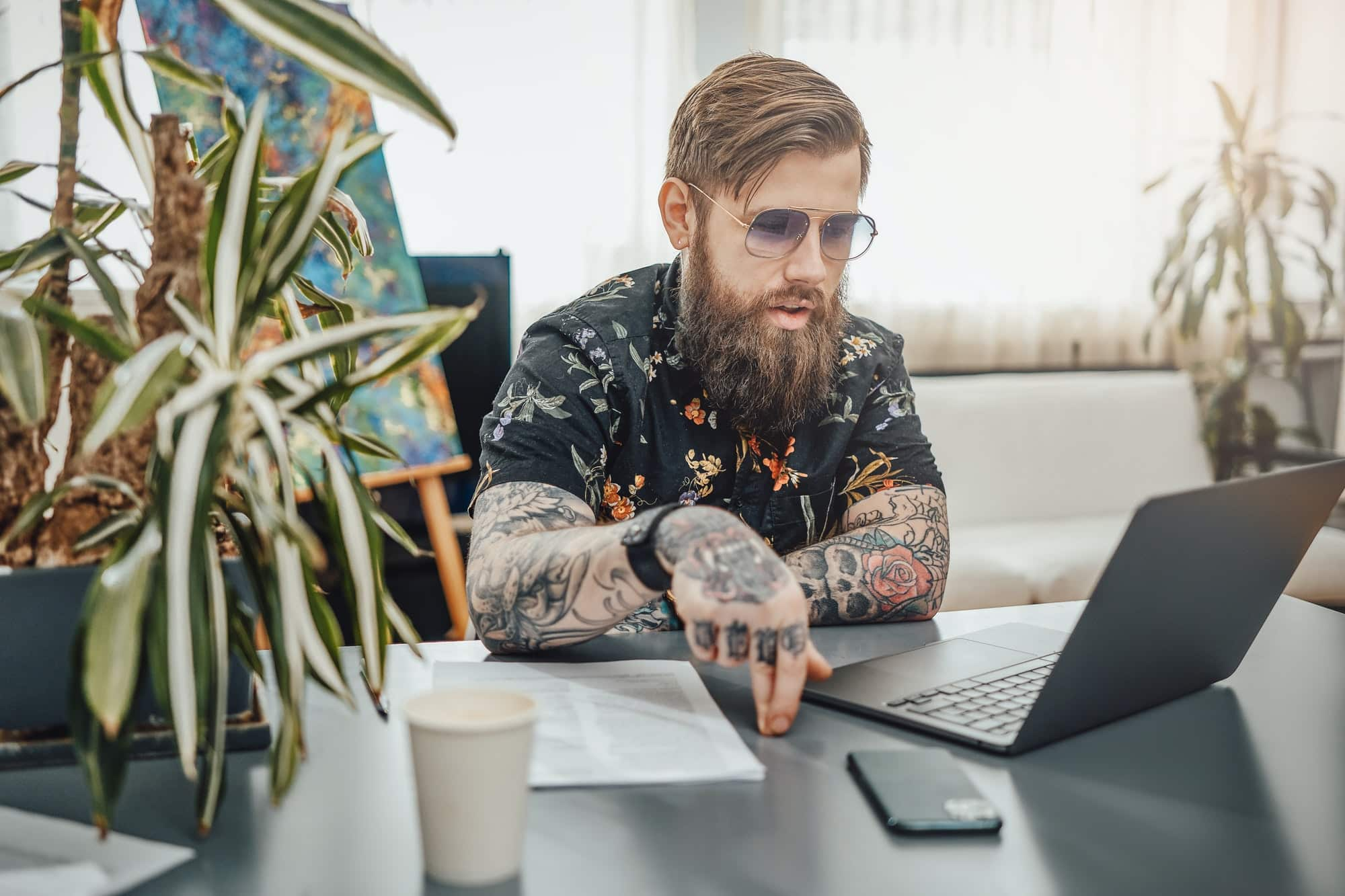 Tattooed and serious business hipster doing his job on a laptop